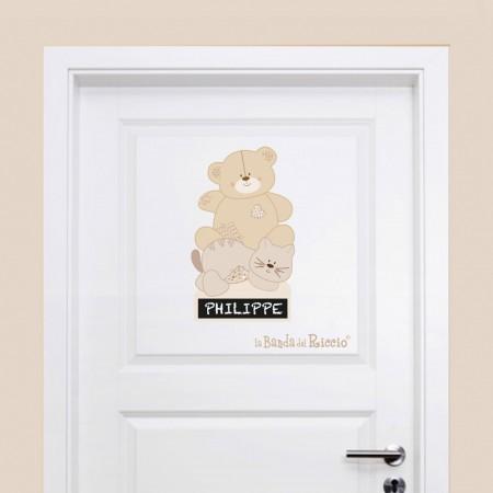 Adesivo porta pupazzi di pezza su una porta in una parete beige